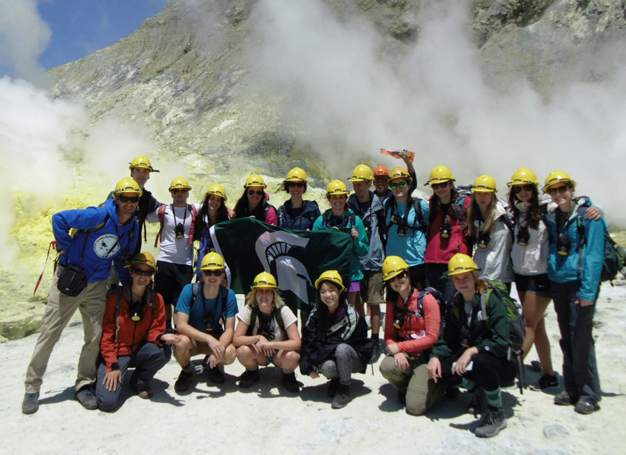 Class photo standing in front of an active volcano