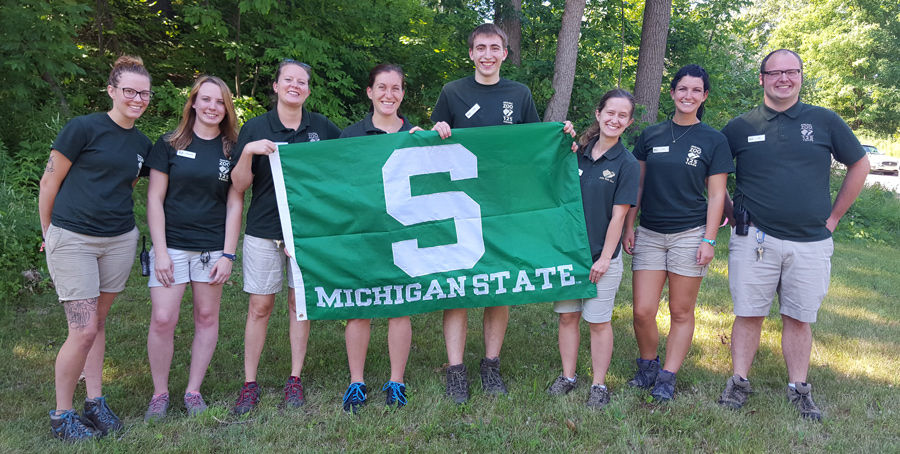 MSU students and alumni working at the John Ball Zoo holding an MSU flag