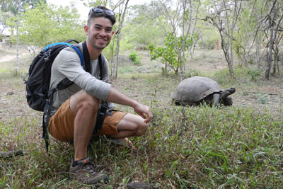 Ryan Grady kneeling near a tortoise during an education abroad trip