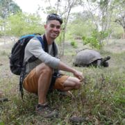 Ryan Grady crouched down near a large tortoise during his study abroad trip