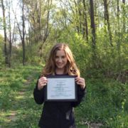 Nicole Thompson standing in a wooded area holding her award certificate