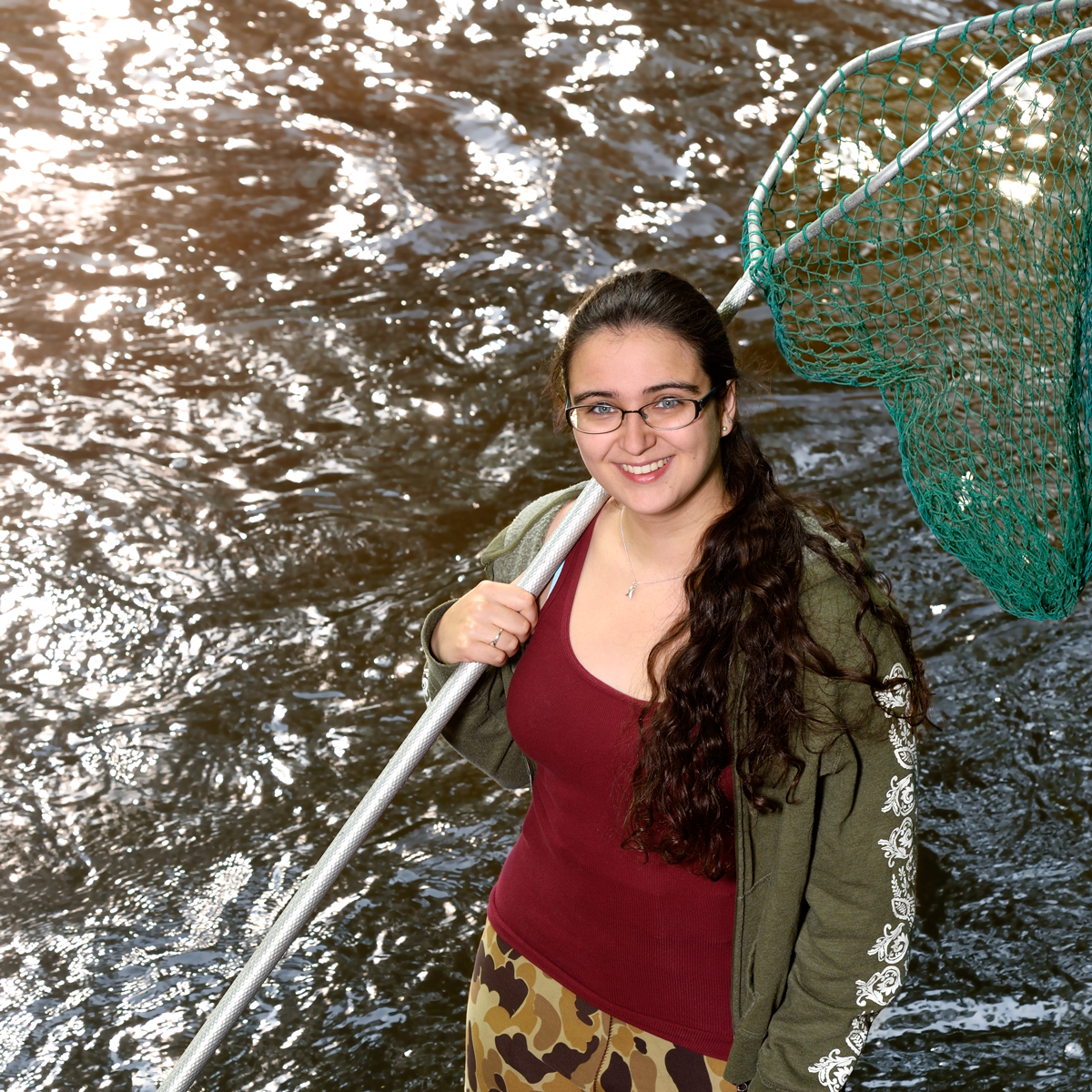 Clara Lepard standing in a body of water holding a net.